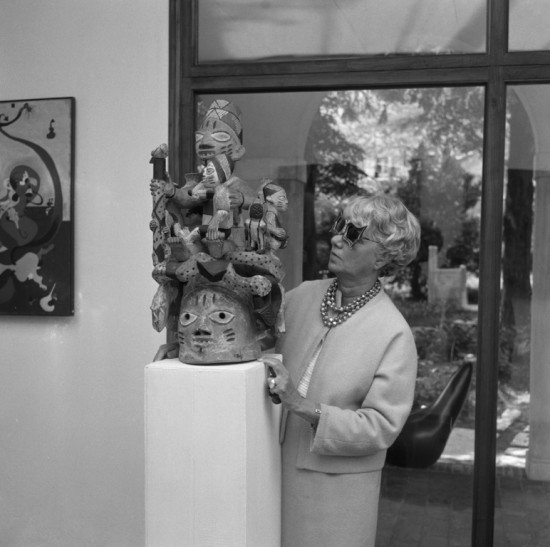 Peggy Guggenheim in the'barchessa' o fPalazzo Venier dei Leoni with her collection of African sculptures; Venice late 1960's